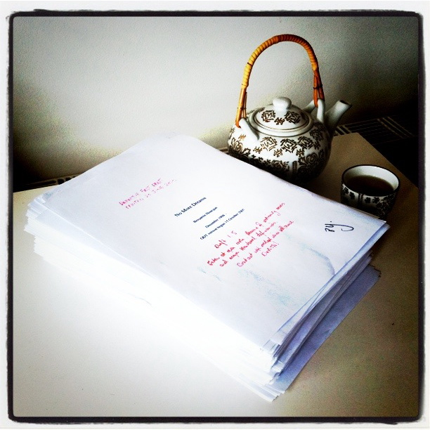 The manuscript of No More Dreams, on a table with an Asian-style teapot with a bamboo handle, and a teacup.